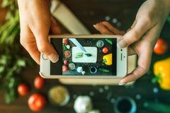 Frauen ` s Hände mit einem Telefon machen Fotos des Gemüses Stockfotografie