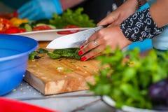Frauen ` s Hände schnitten Frischgemüse Stockfotos