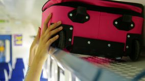 Frauen ` s Hände setzten den Koffer im Regal in den Zug ein stock video footage