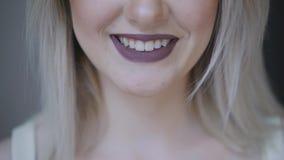 Frauen ` s Lippen werden mit dunklem Lippenstift gefärbt Kussnahaufnahme stock video