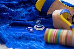Frauen ` s Sandalen mit hohem Absatz auf dem blauen Kleiderblau mit glänzendem Zubehör lizenzfreie stockfotos
