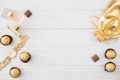 Frauen ` s Satz Zubehör und Bonbons in der goldenen Farbe auf hölzernem Lizenzfreie Stockfotos