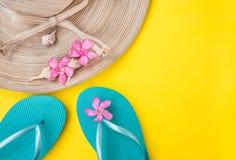 Frauen ` s Strohhut, rosa tropische Blumen, blaue Pantoffel, Meer schält, auf gelbem Hintergrund, Strandferien Lizenzfreie Stockfotos