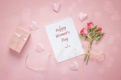 Frauen ` s Tagesgrußmitteilung mit kleinen Rosen, Geschenkbox und hören Stockfotografie