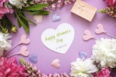 Frauen ` s Tagesgrußmitteilung mit Pfingstrosen, Geschenkbox und decorati Stockfotografie