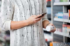 Frauen-Scannen-Flasche mit Smar-Telefon Stockbild