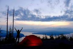 Frauen-Schattenbild, rotes Zelt, Ozean, Wolken und Inseln bei Sonnenaufgang Lizenzfreies Stockbild