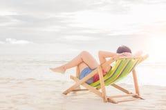 Frauen schlafen auf Strandstuhl am Mittag lizenzfreie stockfotos