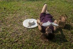 Frauen schlafen Lesebücher auf grünem Gras lizenzfreie stockfotos