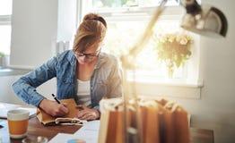Frauen-Schreibens-Anmerkungen über Papiergeschenk bauschen sich auf dem Tisch Lizenzfreie Stockbilder