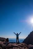 Frauen silhouettieren auf die Oberseite des Berges Stockfotos