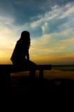 Frauen silhouettieren nahe Meer Stockfotos