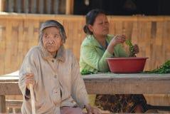 Frauen sitzen außerhalb ihres Hauses am traditionellen Dorf nahe Luang Prabang, Laos lizenzfreie stockfotografie