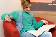 Frauen-Sitzen, trinkend und liest Lizenzfreie Stockfotografie