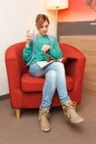 Frauen-Sitzen, trinkend und liest Stockbild