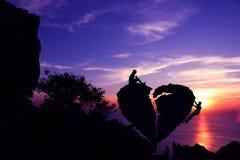 Frauen sitzen und bemannen das Klettern auf defektem Herz-förmigem Stein auf einem Berg mit purpurrotem Himmelsonnenuntergang Lizenzfreies Stockbild