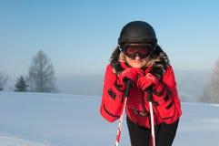 Frauen-Skifahrer in den Bergen in der roten Winterjacke Lizenzfreies Stockfoto