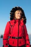 Frauen-Skifahrer in den Bergen in der roten Winterjacke Lizenzfreie Stockfotos