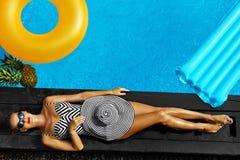 Frauen-Sommer-Mode Sexy Mädchen, das durch Swimmingpool ein Sonnenbad nimmt schönheit Stockfotografie