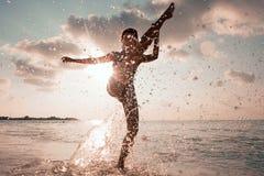 Frauen spritzt im Wasser, im Freien, in der Glättung oder im Morgen lizenzfreie stockfotografie