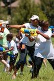 Frauen sprizen Konkurrenten im Gruppen-Wasser-Gewehr-Kampf Stockfotos