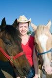Frauen-Standplätze, die mit Pferden - Vertikale lächeln Lizenzfreies Stockbild