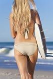 Frauen-Surfer im Bikini mit Surfbrett am Strand Lizenzfreies Stockbild
