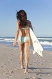 Frauen-Surfer im Bikini mit Surfbrett am Strand Stockbild