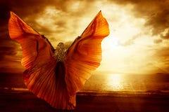 Frauen-Tanzen-Flügel-Kleid, Mode Art Model Flying auf Ozean-Himmel stockfotos