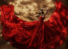 Frauen-Tanzen im roten Kleid, Mode-Modell-Dance Flying Gown-Gewebe lizenzfreie stockfotografie