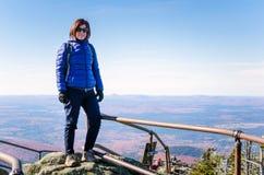 Frauen-Tourist auf der Spitze eines Berges und des blauen Himmels Stockbilder