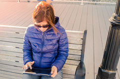 Frauen-Tourist, der draußen ein Tablet unter einem warmen Abend-Sonnenlicht verwendet Lizenzfreies Stockbild