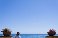 Frauen-Tourist, der heraus dem Ozean betrachtet Stockfotografie