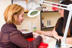 Frauen-tränkende Hände während der Badekurort-Maniküre Lizenzfreies Stockfoto