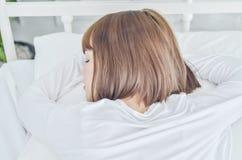 Frauen tragen weiße Pyjamas auf der Matratze lizenzfreies stockbild