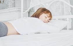Frauen tragen weiße Pyjamas auf der Matratze lizenzfreies stockfoto