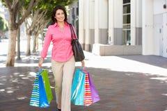 Frauen-tragende Einkaufstaschen auf Stadt-Straße Stockfoto