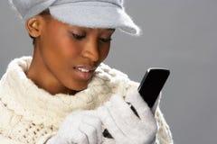 Frauen-tragende Strickwaren im Studio unter Verwendung des Mobiles Lizenzfreies Stockbild