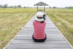 Frauen-tragender Hut, der auf einer Holzbrücke mit einer Bambushütte auf den Reisgebieten sitzt lizenzfreie stockbilder