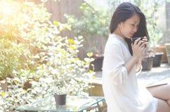 Frauen trinken Garten des Kaffees morgens lizenzfreie stockfotos