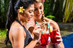 Frauen an trinkenden Cocktails des asiatischen Hotelpools Lizenzfreie Stockfotografie
