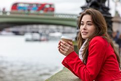 Frauen-trinkender Kaffee durch Westminster-Brücke, London, England lizenzfreie stockfotografie