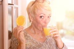 Frauen-trinkender Saft und Halten der orange Scheibe Lizenzfreie Stockfotografie