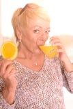 Frauen-trinkender Saft und Halten der orange Scheibe Lizenzfreies Stockfoto