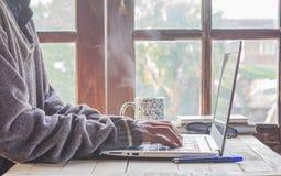 Frauen und Computer zu Hause Holz und Kaffee stockbild
