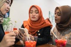 Frauen und Freunde Hijab traurig, wenn schlechte Nachrichten gelesen werden stockfoto