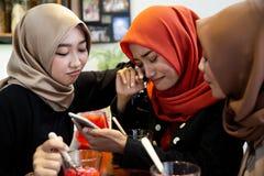 Frauen und Freunde Hijab traurig, wenn schlechte Nachrichten gelesen werden lizenzfreie stockfotografie