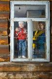 Frauen- und Kindblick im Fenster Lizenzfreies Stockfoto