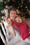 Frauen- und Mädchenfall spielt auf der Weihnachtsgirlande die Hauptrolle Stockfotos