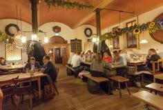 Frauen und Männer, die Bier innerhalb des traditionellen Restaurants in der alten bayerischen Art essen und trinken stockfotografie